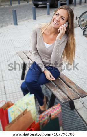 Attractive young woman sitting on the bench after shopping and talking on mobile phone