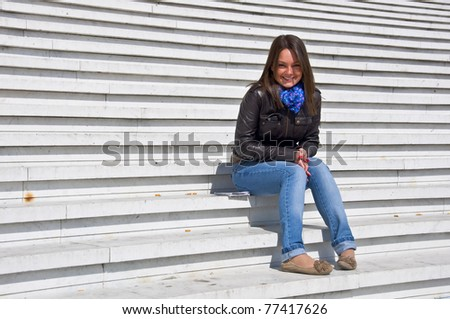 Attractive young woman sitting on the marble steps and smiles in the sunlight.