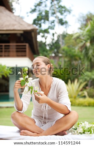Attractive young woman smelling tropical flowers in an exotic spa garden.