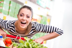 Attractive young woman smiling and pushing a cart at supermarket.