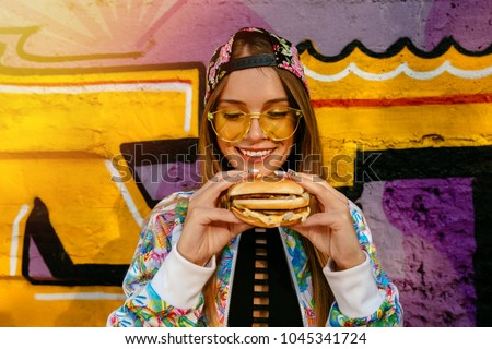 Attractive young woman, smiling cheerfully, holds tasty burger in two hands. Dressed in colorful jacket and cap, in sunglasses. Outdoors, near the wall with graffiti.