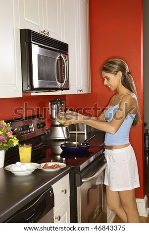Attractive young woman smiling in her kitchen while cooking breakfast. She is dressed in sleepwear. Vertical shot.