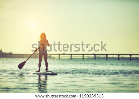 Attractive young woman stand up paddle surfing