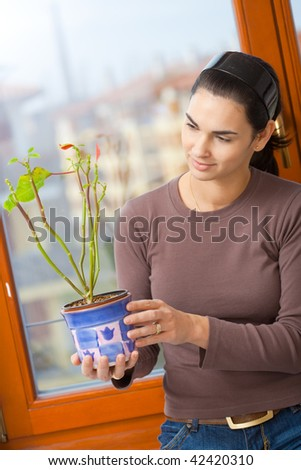 Attractive young woman standing at window, holding green potted plant, smiling.