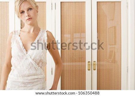 Attractive young woman standing in bedroom by wardrobe wearing a pretty night dress. - stock photo