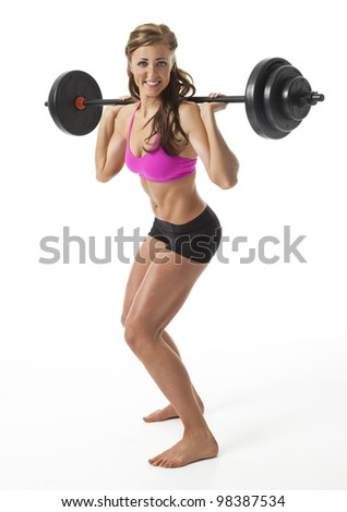 Attractive young woman standing with barbell on shoulders against white background.