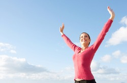 Attractive young woman standing with her arms outstretched up in the air above her head, joyfully smiling against an intense blue sky during a sunny day.