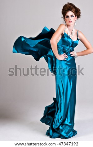 Attractive young woman standing with her hands on her hips in a blue satin, wind blown dress. Vertical shot.