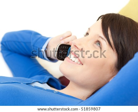 Attractive young woman talking on phone lying on a sofa in the living-room