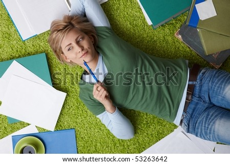 Attractive young woman thinking on floor, looking aside, pen in hand, surrounded by books and notes. - stock photo