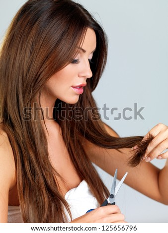 Attractive young woman trimming the ends of her long brunette hair with a pair of scissors to remove split ends