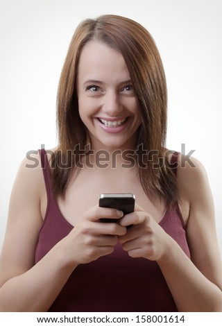 Attractive young  woman using her cell phone to send a text message