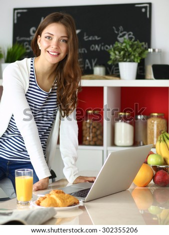 Attractive young woman using laptop and sitting in the kitchen . #302355206