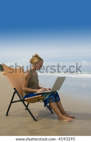 attractive young woman using notebook computer in comfortable chair