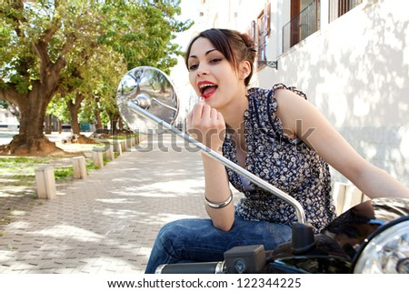 Attractive young woman using the mirrors on her motorbike to apply red lipstick on herself on a sunny day, outdoors.