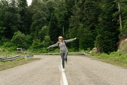 Attractive young woman walks along the line of the road with hands raised enjoying nature.
