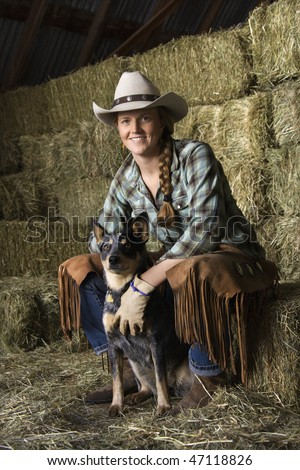 Attractive young woman wearing a white cowboy hat. She is sitting on hay and smiling while holding an Australian Shepherd. Vertical shot.