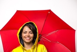 Attractive young woman wearing a yellow raincoat and holding a red umbrella