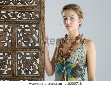 Attractive young woman wearing an exotic outfit and jewelry and leaning on a carved wood screen panel while on vacations.