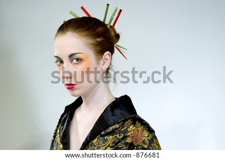 Attractive young woman wearing elaborate makeup with chopsticks in her hair bun
