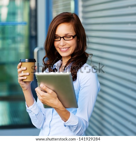 Attractive young woman wearing glasses drinking coffee and reading her touchscreen tablet while standing outside a commercial building