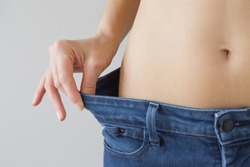 Attractive young woman wearing jeans and showing slim body after sport trainings and healthy eating. Weight loss concept.
