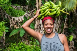 Attractive young woman with a bunch of green bananas on her head