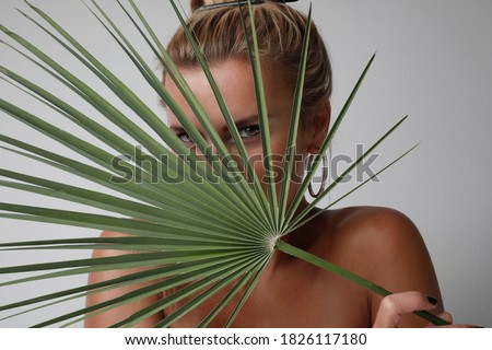 Attractive young woman with blonde hair, looking at the camera and holding palm leaf. Beauty and natural skin concept.