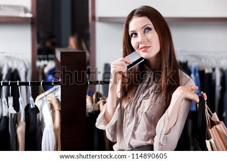 Attractive young woman with credit card is in the shopping mall