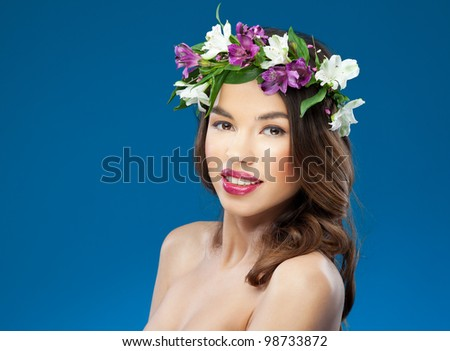 Attractive young woman with flowers on the head looking to the camera on the blue background