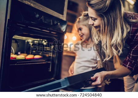 Attractive young woman with her little cute daughter are cooking cakes on kitchen.