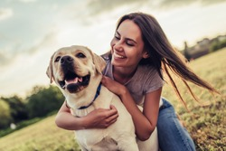 Attractive young woman with labrador outdoors. Woman on a green grass with dog labrador retriever.