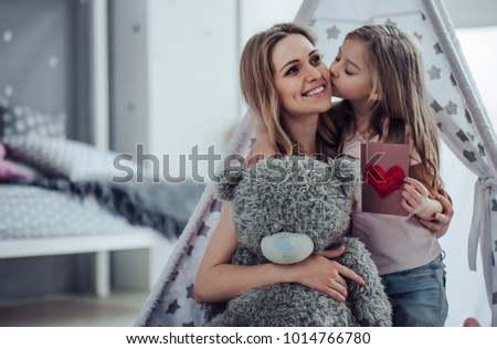 Attractive young woman with little cute girl are having fun together at home. Mom and daughter are sitting on the floor, hugging, kissing and smiling. Happy family concept. Mother's day. #1014766780