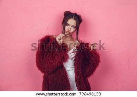 Attractive young woman with lollipop in hands on a pink background.