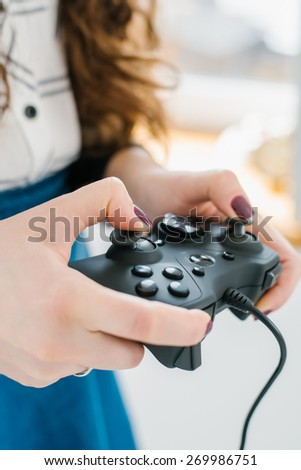 Attractive young woman with long curly brunette hair on a background window playing computer game at home.