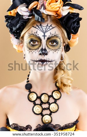 Stock Photo attractive young woman with sugar skull makeup. Mexican Day of the dead woman wearing sugar skull makeup and flower wreath.