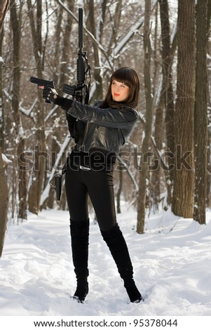 Attractive young woman with weapon in their hands