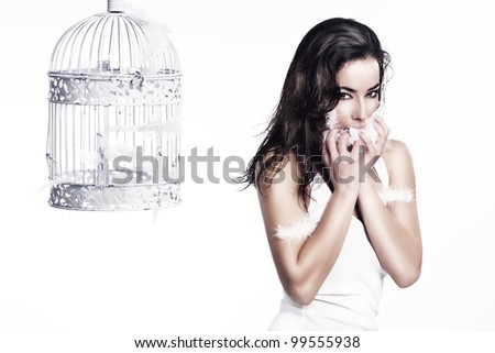 attractive young woman with white feathers in hands and mouth stand beside an empty birdcage