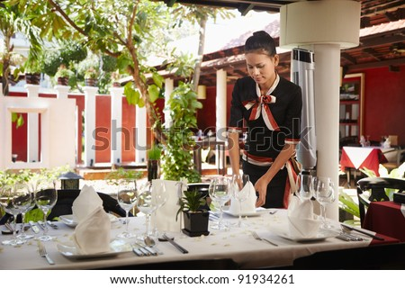 Attractive young woman working as waitress in exclusive restaurant, setting up a table. Waist up, front view