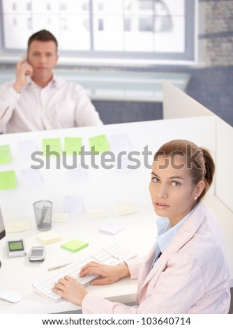 Attractive young woman working on computer in bright office, man on phone in the background.