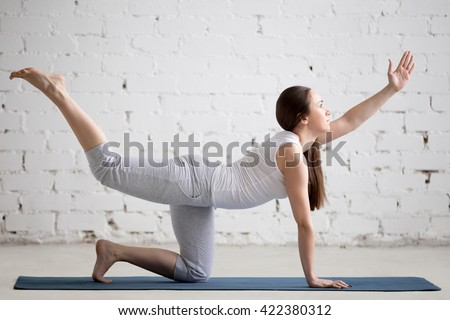 Attractive young woman working out indoors. Beautiful model doing exercises on blue mat in room with white walls. Pilates Bird-dog or Donkey Kick exercise (chakravakasana). Full length