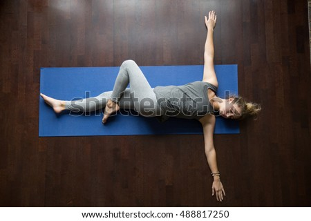 Photo of  Attractive young woman working out indoors, doing yoga exercise on wooden floor, lying in Reclining Spinal Twist, Jathara Parivartanasana, resting after practice, full length, top view