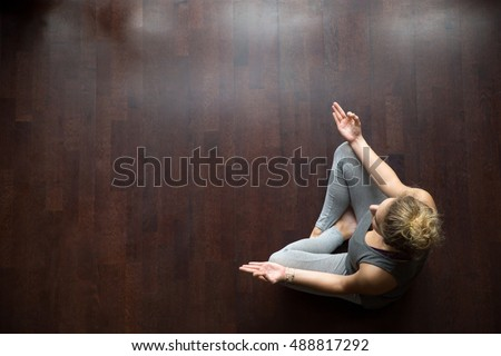 Attractive young woman working out indoors, doing yoga exercise on wooden floor, sitting in Easy (Decent, Pleasant Posture), meditating, breathing, relaxing. Full length. Top view. Copy space