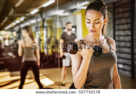 Attractive young woman working out with dumbbells at a gym.