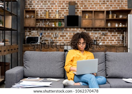Photo of attractive young woman working working with laptop on couch