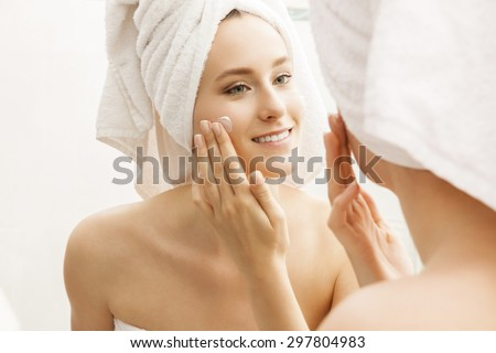 Attractive Young Woman Wrapped with Bath Towels, Applying Cream on her Face After a Shower at the Bathroom.