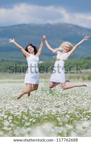 Attractive young women jumping in chamomile field with raised hands