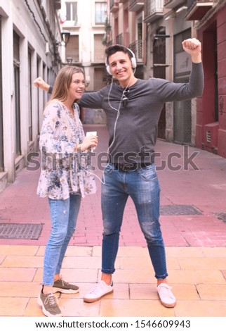 attractive young young couple listen music with headphones in the street