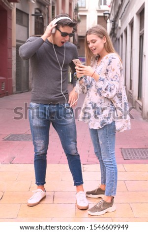 attractive young young couple listen music with headphones in the street #1546609949