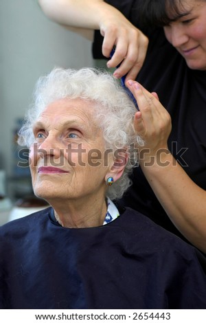 Attractivr senior getting her hair styled at a beauty salon.